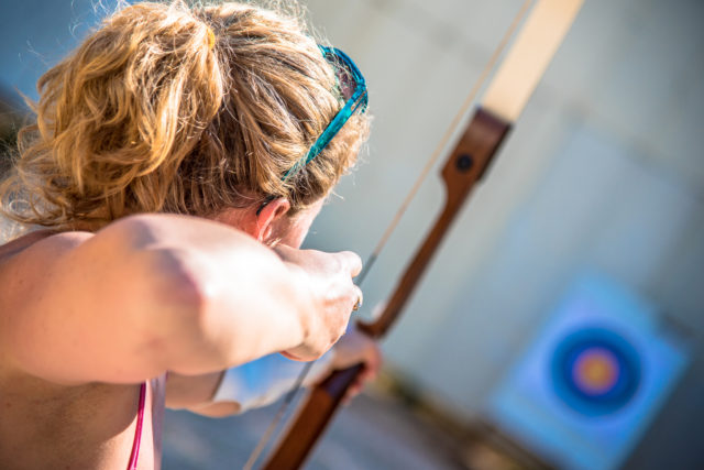Young woman aiming with a bow