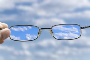 out of focus sky with hand holding a glasses that correct the vision